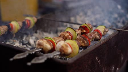 espetos : Kebab on skewers cooked on the grill close-up. Shish kebab on skewers. Cooking over charcoal. Shot in slow motion