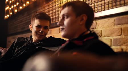 косплей : Two friends in Halloween costumes chatting carefreely in a dark cozy cafe. Close-up portrait of guys celebrating the holiday. Shot in slow motion