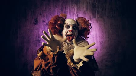 scary clown : Scary clown with colorful makeup suddenly appears in the frame and frightens the viewer. Slow motion shooting against a dark background