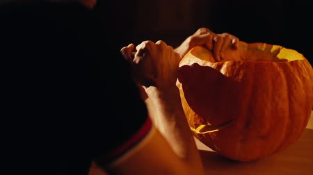 salva : Man is carving a holiday pumpkin for Halloween celebration in a dark room. Close-up of unrecognizable mans hands cutting details of a Jack O Lantern pumpkin decoration.