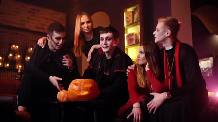 косплей : Young man in festive priest costume hugs his girlfriend at Halloween meeting of friends in cafe. Guy in the image of Count Dracula tells stories. Holiday carved pumpkin on table. Shot in slow motion