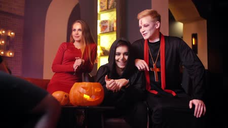 косплей : Friends in colorful festive costumes and with makeup on their faces have fun at Halloween party in a cafe. Holiday carved pumpkin on table. Shot in slow motion