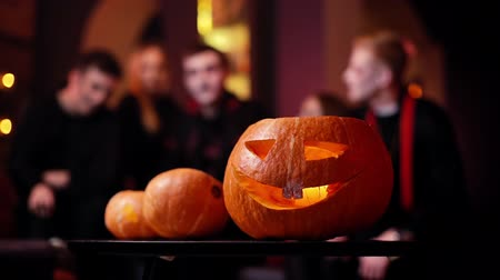 salva : Halloween carved pumpkin on the table at the cafe. Against the background of a group of friends celebrating on the eve of Saints Day. Theres a candle burning inside the pumpkin. Shot in slow motion