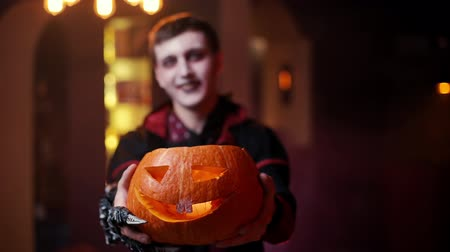 косплей : Young man in a Halloween costume of Count Dracula holding a carved pumpkin and smiling at the camera. A blurred face of a man in the background. Shot in slow motion