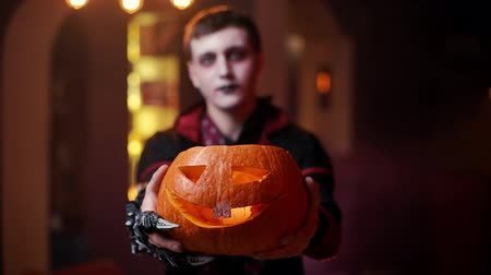 vampiro : Young man in a Halloween costume of Count Dracula raises a carved pumpkin and looking seriously into the camera. A blurred face of a man in the background. Shot in slow motion