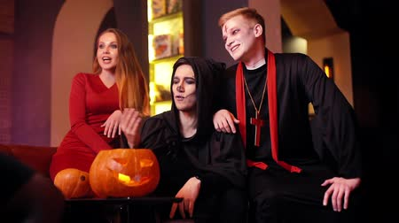 косплей : Beautiful sexy girl in the company of two guys festively dressed in Halloween costumes has fun in a cafe. Group caucasian student are celebrate Halloween. Shot in slow motion