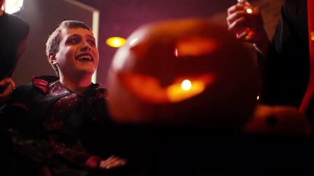 косплей : Young man in Count Dracula costume sits surrounded by friends in dark cafe. Happy company of friends celebrating Halloween. On the table in the foreground is a carved pumpkin, a symbol of Halloween. Стоковые видеозаписи
