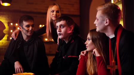 косплей : Young man in a festive priest costume hugs his girlfriend at a Halloween meeting of friends in a cafe. The guy in the image of Count Dracula tells terrible stories. Shot in slow motion Стоковые видеозаписи