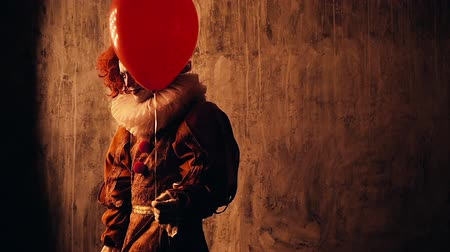 косплей : Creepy clown with colorful makeup in a carnival costume goes into the dark. Shooting in slow motion on dark red background