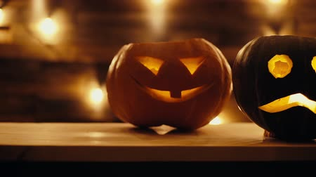 bizarre : Close-up three Halloween pumpkin with burning candle inside in dark room. Holiday Jack-O-Lanterns with scary luminous faces on the background of the wall with bright garland. Close-up tracking shot