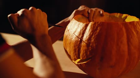 vytesaný : Close-up man is carving a holiday pumpkin for Halloween celebration in a dark room. Close-up of unrecognizable mans hands cutting details of a Jack O Lantern pumpkin decoration. View from behind.