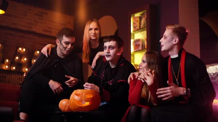 косплей : Young people are celebrating Halloween in cafe. Group of young cheerful guys and girls dressed in holiday costumes are sitting in room with red walls. Carved pumpkin on table. Shot in slow motion Стоковые видеозаписи