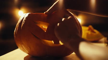 マスコット : Man is completing the creation of the Halloween festive pumpkin, hand close-up. Man squeezing out a piece of pumpkin - the eye.