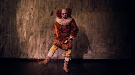 psycho : Crazy scary clown dancing against a dark red wall in darkened room. Terrible clown with colorful makeup in a festive costume. Shooting in slow motion