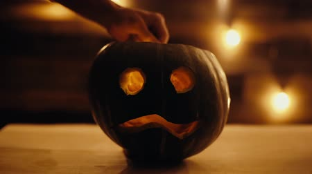 fire arms : Man lights a candle inside a Halloween pumpkin with match in dark room. Mans hand creates festive lantern, close-up in slow motion on the background of the wall with bright garland.