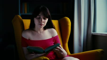 roman : Beautiful girl reads a book at home. Pretty cute young woman in a red dress sits on a yellow soft chair and reads a book, flips through the page. Shot in slow motion in dark room near the window