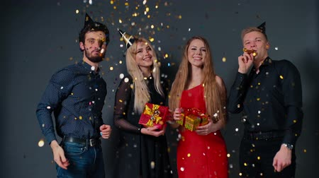apito : Two cheerful guys blow a festive whistle and throw up a colorful confetti. Two beautiful happy girl are holding bright gift boxes in hands. Shooting in slow motion on isolated dark background.