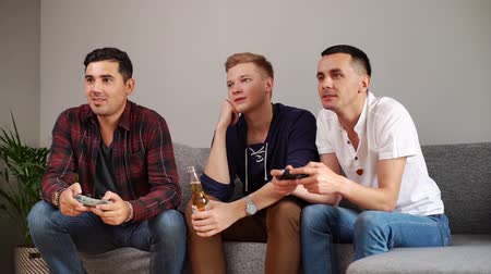 pátek : Joyful young men playing video game console. Three friends playing video game on home. Video game and leisure concept Dostupné videozáznamy