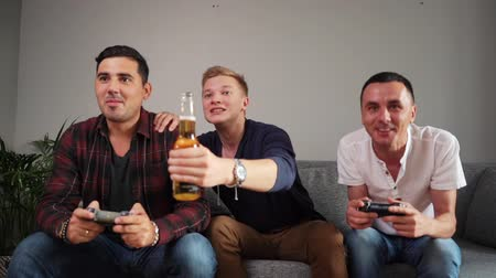 konsola : Fun company of friends is excited to playing video games. Guy is emotionally celebrating the victory over his friend in the console game. Video game and leisure concept