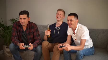 beer house : Three handsome young friends having fun on evening playing video games with excellent mood in modern living room. Video game concept. Guy laughs loudly at his friends game. Shotting in slow motion.