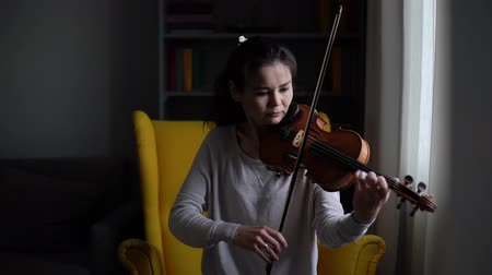 hegedűművész : Young woman playing the violin in slow motion, sitting on soft chair in room with a modern interior. Girl is practicing playing musical instrument at home. Stock mozgókép