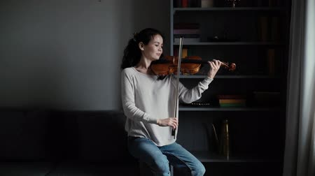 バイオリニスト : Beautiful young woman violinist plays the violin at home in slow motion, sitting on the couch