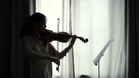 hegedűművész : Beautiful female looks at the score while playing the violin by the window in slow motion. Girl is practicing playing musical instrument at home.