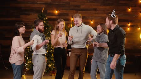 шесть : Cheerful young friends are clinking with champagne glasses and celebrating New Year. Christmas tree with garland and festive illumination in background. Friends are celebrating Christmas Eve.