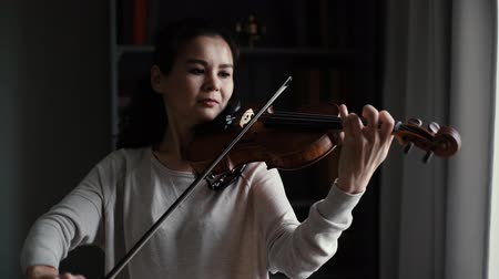 hegedűművész : Lovely young woman plays the violin in slow motion in a room with a modern interior. Girl is practicing playing musical instrument at home. Stock mozgókép