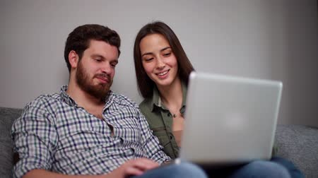 antwoord : Handsome guy and beautiful girl is sitting on soft sofa and using laptop. Young man shakes his head negatively to answer his girlfriends question. Shooting in slow motion.
