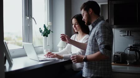 rassembler : Charming young woman working behind a laptop next to a window in the kitchen. Guy brings his girlfriend a glass of coffee. Young bearded man looks at the laptop screen and kisses his girlfriend.