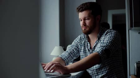 correspondência : Handsome bearded man typing on laptop keyboard. Businessman works on notebook. Tracking shot in slow motion.