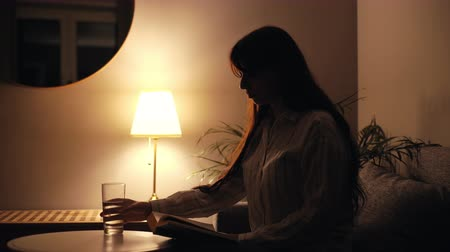 교과서 : Concentrated young woman reads a book in dark living room and makes a sip of water out of a glass. Light from a desk lamp.