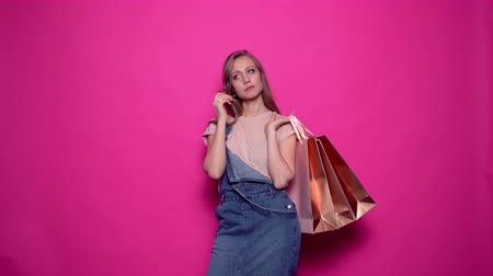 durulması : Beautiful young woman is cries, wipes her eyes and smiles while holding shopping bags on pink background. Cheerful girl in denim clothes posing with packages in professional studio.