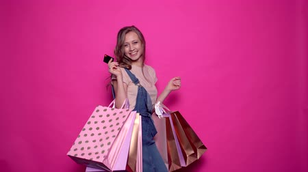 segunda feira : Smiling young woman in denim clothes holding credit card and colorful shopping bags in hands on isolated pink background. Cheerful girl posing with packages on season sale in professional studio.