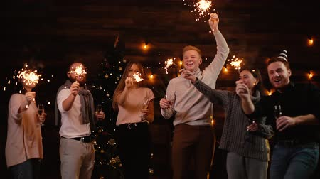 bengália : Group of young cheerful friends dance with Bengali lights, have fun and carefree time celebrating New Year. People dancing with sparklers on dark room and clinking with champagne glasses. Stock mozgókép