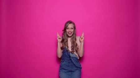 suceder : Cheerful smiling young woman is standing with fingers crossed for good luck. Charismatic girl is showing concept of emotions in professional studio.