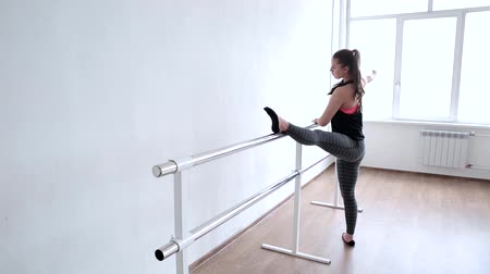 instrutor : A young girl is an aspiring dancer. Girl ballerina with lush hips performs ballet exercises in the Studio.