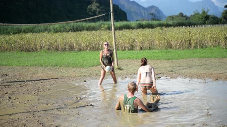 volleyball : Vang Vieng, Laos - November 13, 2014 : Foreign tourists enjoying a game of volleyball with mud at Vang Vieng, Laos