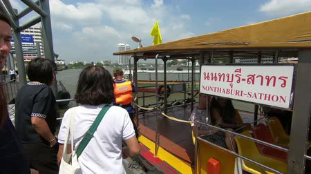 phraya : Bangkok, Thailand - March 5, 2018 : People at the Prannok Pier get on an yellow flagged tourist boat of the Chao Phraya Express Boat, a transportation service operating on the Chao Phraya River