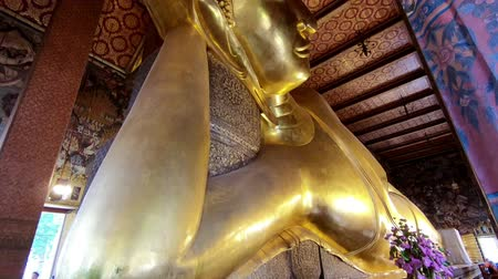 worship : Reclining Buddha gold statue face in Wat Phra Chetupon Vimolmangklararm (Wat Pho) temple in Thailand Stock Footage