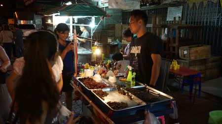 Çin mahallesi : Bangkok, Thailand - May 3, 2018 : Unidentified man sells street exotic food. Dried insects, bugs, worms, scorpions and frogs at Yaowarat Road in Bangkoks Chinatown district