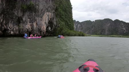 surat : Phuket, Thailand - June 1, 2018 : Tourists in life jackets approaches a cliff in the sea in active wear on kayak boat
