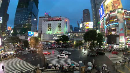 cruzamento : Tokyo, Japan - June 20, 2018 : Time lapse video of people with umbrellas cross the famous diagonal intersection in Shibuya, Tokyo, Japan