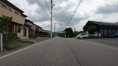 subúrbio : Yamanashi, Japan - June 22, 2018 : POV driving on a road through a Japanese village at Fujikawaguchiko, Japan Stock Footage