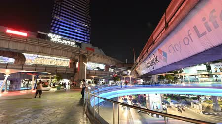 nákupní centrum : Bangkok, Thailand - December 5, 2018 : Night time lapse view traffic of BTS sky train and car with crowd people walking at Siam Square sky walk