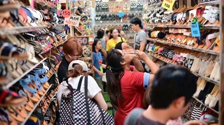 иностранец : Bangkok, Thailand - June 9, 2019 : Unidentified customer selecting shoes at Chatuchak weekend market Стоковые видеозаписи