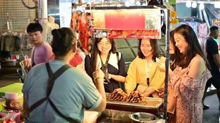 Bangkok, Thailand - June 9, 2019 : Khaosan Road street vendor sell street food with women chinese tourist