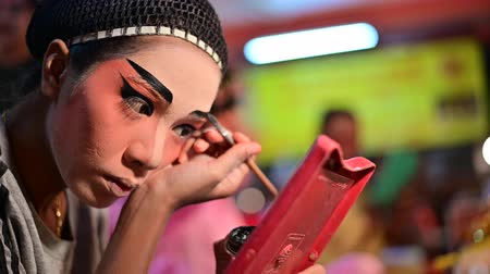Bangkok, Thailand - October 2, 2019 : Chinese opera performer prepares for a show and applies paint to turn his face into a mask Vídeos