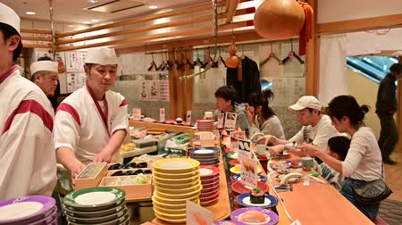Fukuoka, Japan - November 13, 2019 : Japanese people and foreign travelers eating sushi from sushi conveyor belt